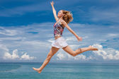 Happy young woman jumping on the background of the azure sea — Stock Photo