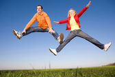 Happy smiling couple jumping in sky — Stock Photo