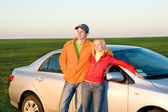 Glada unga par med ny bil — Stockfoto