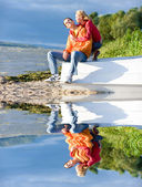Young love Couple sit on boat on bank of river — Stock Photo