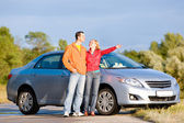 Happy young couple with their new car. Woman show something by h — Foto Stock