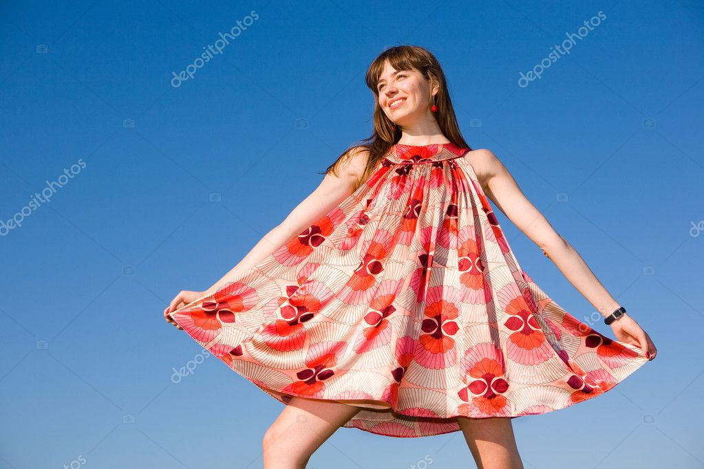 Happy girl fleeing on a meadow. In red dress and red shoes ...
