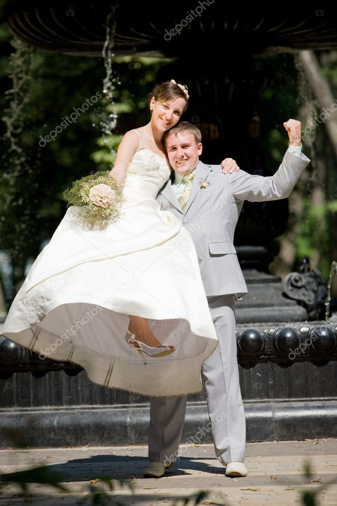Groom and bride joy against backdrop fountain — Stock Photo #4708601
