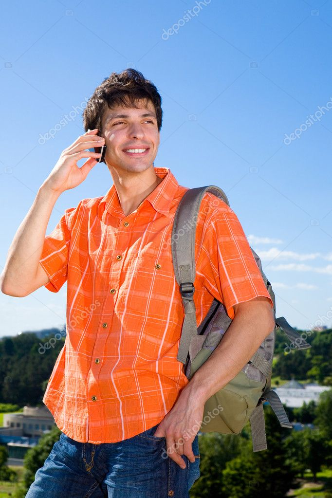 Young man from the phone calls. It was on Mount. Against a blue sky with clouds  Stock Photo #4708622