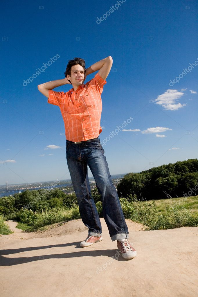 Young man winning on peak of a mountain. Against a blue sky with clouds. — Stock Photo #4708623