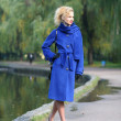 Beautiful blonde outdoors in coat and hat — Stock Photo
