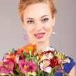 Beautiful young woman in light dress with flowers on gray backgr — Stock Photo #4710297