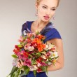 Beautiful young woman in light dress with flowers on gray backgr — Stock Photo