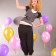 Beautiful young girl in light dress on background balloons — Stock Photo