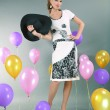 Beautiful young girl in light dress a hat on background balloons — Stok fotoğraf