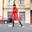 Girl in a red coat moves outdoors — Stock fotografie