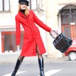 图库照片: Girl in a red coat moves outdoors