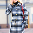 Royalty-Free Stock Photo: Beautiful young blond in a coat talks on the phone. Photography