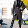 Beautiful blonde in coat and hat standing outdoors - Stockfoto