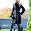 Beautiful blonde in coat and hat standing outdoors - Foto Stock
