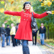 Happy woman in red throwing leaves in the air — Foto de Stock