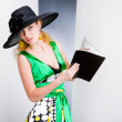 Young Woman in a green dress and black hat. In the studio — Stock Photo