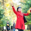 Happy woman in red throwing leaves in the air - Stock Photo