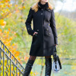 Beautiful blonde in coat and hat standing outdoors — Stock Photo