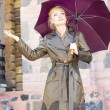 Beautiful Young Woman with umbrella Against the backdrop of bui — Stock Photo