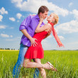 Beautiful young couple kissing on the grass — Stock Photo