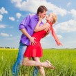 Beautiful young couple kissing on the grass - Stock Photo