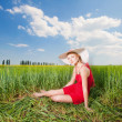 Girl in a hat sitting on the grass - Stock Photo