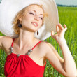 Girl in a hat sitting on the grass — Stock Photo