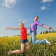 Happy is jumping in field — Stock fotografie