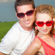 Young love Couple smiling in glasses heart under blue sky — Stock Photo