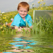 Smiling child with laptop computer on meadow. Reflected in Water — Stock Photo