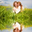 Mother and daughter lay on a grass with a notebook — Stock Photo #4710809