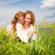 Mother and daughter lay on a grass with a notebook — Stock Photo