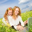 Mom and Daughter with laptop resting on meadow — Stock Photo