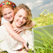 Mother and daughter lay on a grass with a notebook — ストック写真