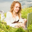 Young woman sitting on the grass field with a laptop. Against th — Stock Photo