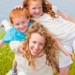 mère avec enfants s'amuser sur le terrain — Photo #4711176
