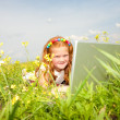 Girl with laptop resting on meadow. — Stock Photo
