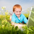 Smiling child with laptop computer on meadow — Stock Photo