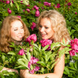 Two happy young women in flowers — Stock Photo