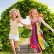 Two happy young women are runing in a park — Stock Photo