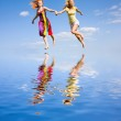 Two happy girls fleeing on a water under the blue sky. — Stock Photo #4711309