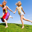 Two happy young women are runing in a field — Stock Photo #4711318