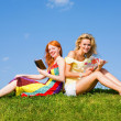 Two beautiful girls with notebook outdoors. Sitting on the green — Stock Photo #4711321