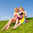 Two beautiful girls with notebook outdoors. Sitting on the green - Stock Photo