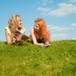 Two beautiful girls with notebooks outdoors. Lay on the green gr - Foto de Stock