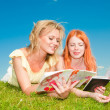 Two beautiful girls with notebooks outdoors. Lay on the green gr — Stock Photo #4711333