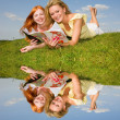 Two beautiful girls with notebooks outdoors. Lay on the green gr — Stock Photo #4711341