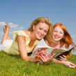 Two beautiful girls with notebooks outdoors. Lay on the green gr — Stock Photo