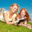 Royalty-Free Stock Photo: Two beautiful girls with notebooks outdoors. Lay on the green gr
